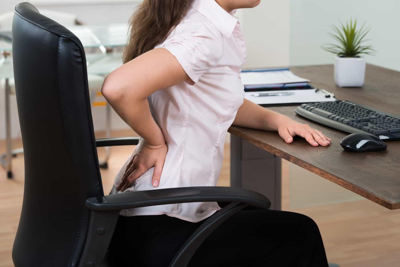 Employée ayant mal au dos car elle n'a pas de chaise de bureau ergonomique