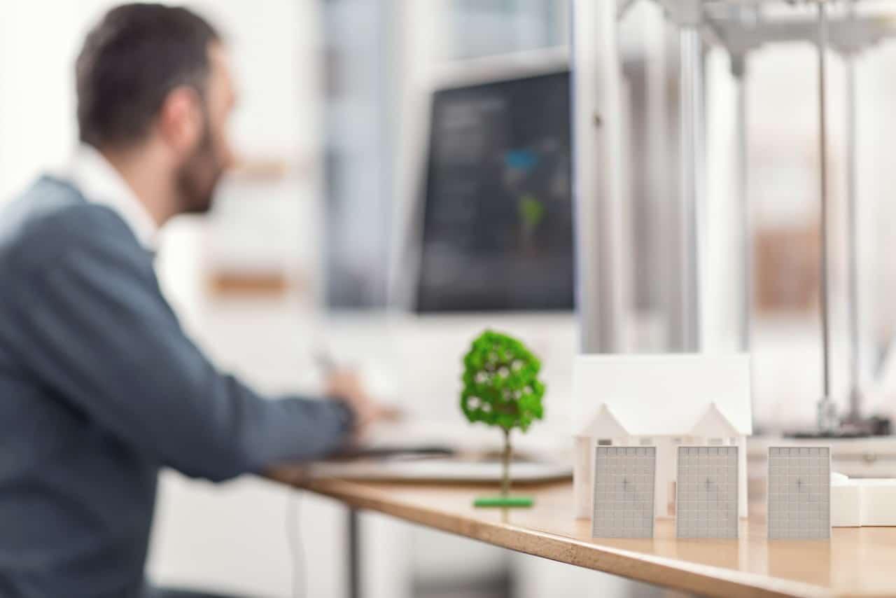 Homme à son bureau, arbre vert sur le bureau pour impliciter le fait d'imprimer de manière écologique